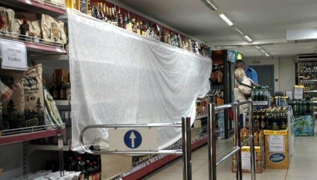 Regály s alkoholom sú po 23. hodine v obchodoch zahalené takýmito plachtami.